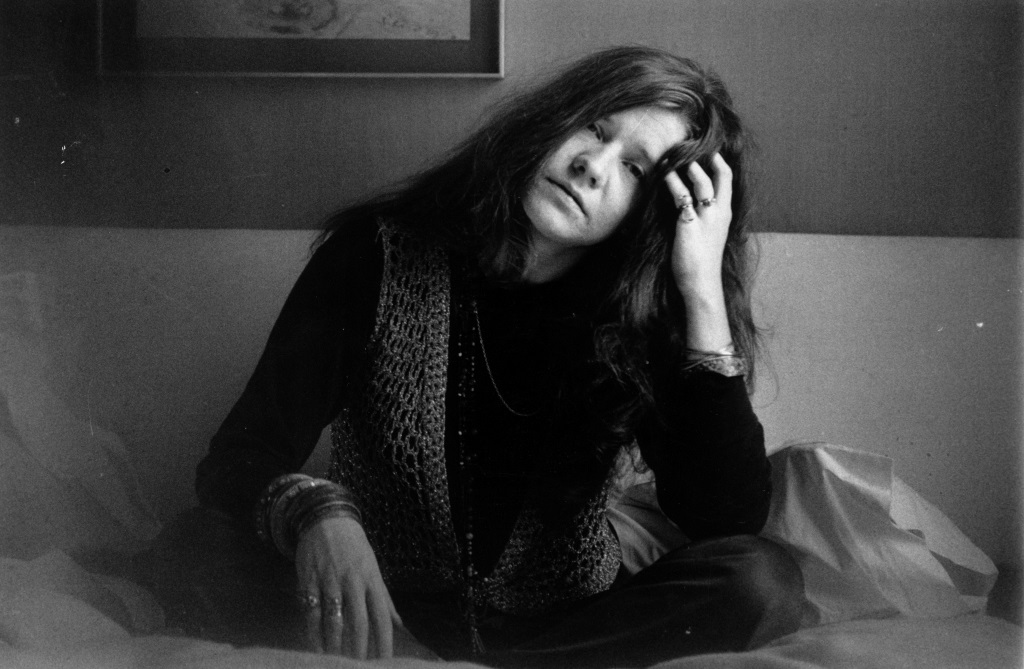 This is a black and white photo of Janis Joplin sitting down a couch resting her head on her hand.