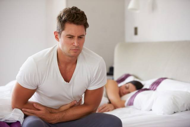 man sitting on the bed clutching his stomach