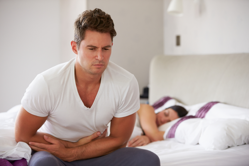 A man sitting on the bed holding his stomach