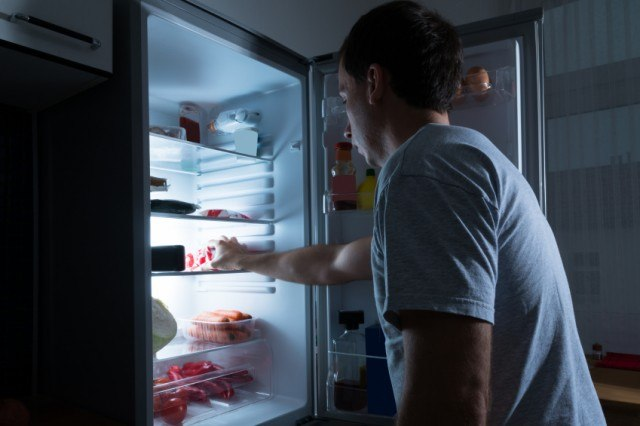 Man going for a late-night snack in the fridge