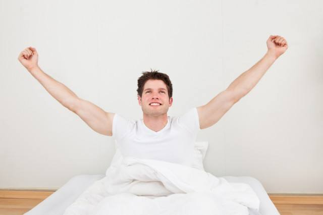 a man raising his arms in bed