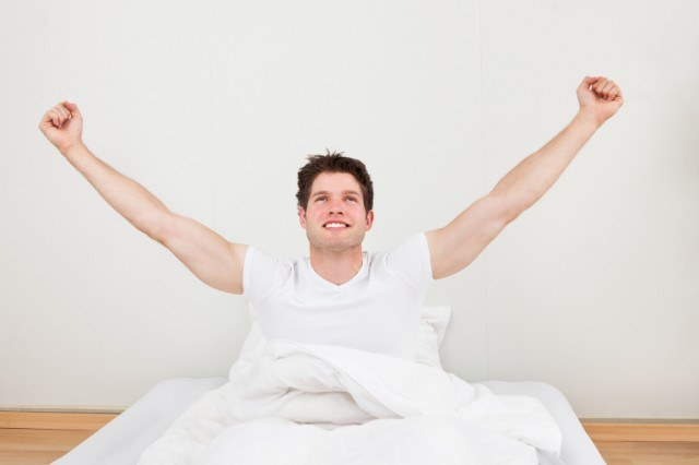 Happy man waking up, stretching in bed