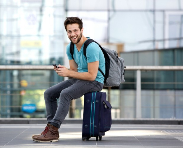 man sitting on his suitcase with a phone