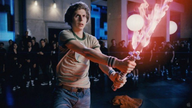 Michael Cera holds a flaming sword in front of a crowd in Scott Pilgrim vs. the World