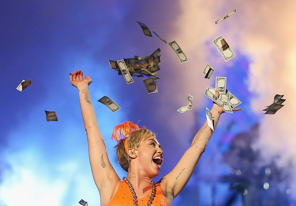 Miley Cyrus throwing money in the air on stage.