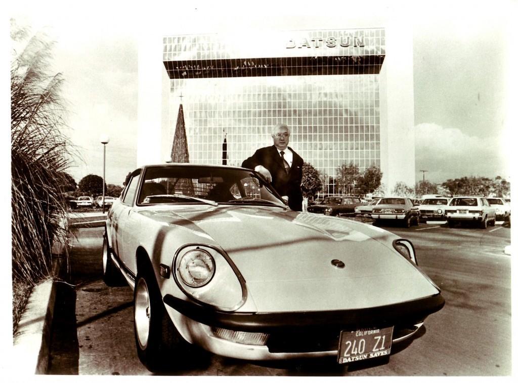 A vintage photograph of Yutaka Katayama posing with a Datsun 240Z.