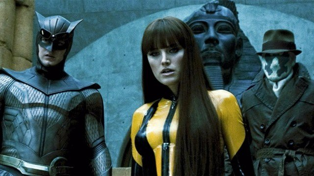 Patrick Wilson as Nite Owl, Malin Akerman as Silk Spectre, and Jackie Earle Haley as Rorschach dressed in costume in front of an Egyptian statue in Watchmen