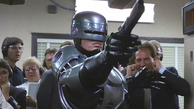 Robocop stands in front of a crowd in a hallway and is pointing a gun in the opposite direction.