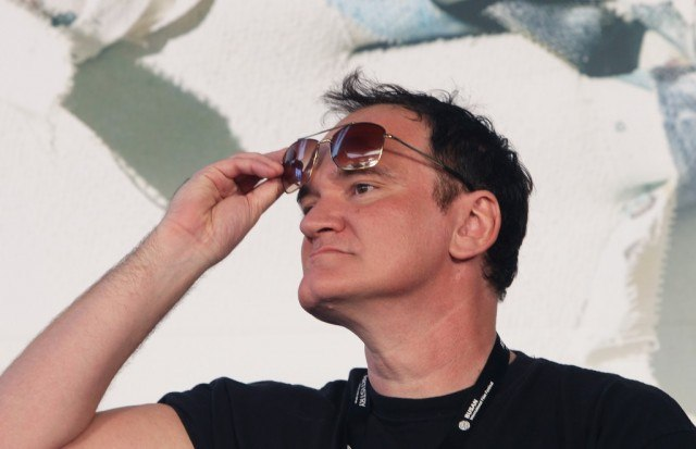 Quentin Tarantino is looking to the side and is lifting his sunglasses from his eyes.