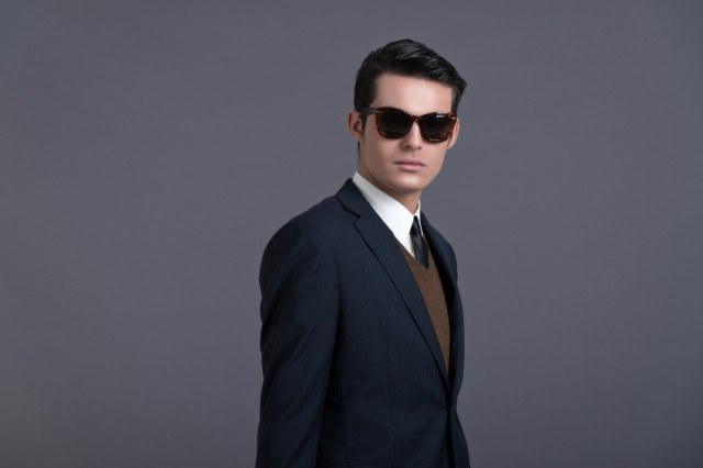 Man wearing a sweater, suit and sunglasses.