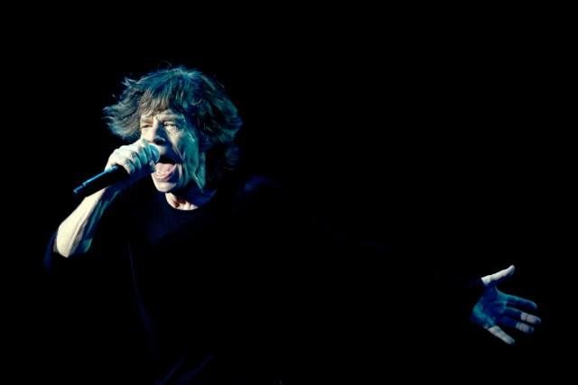 Mick Jagger holding a microphone and performing on a dark stage.