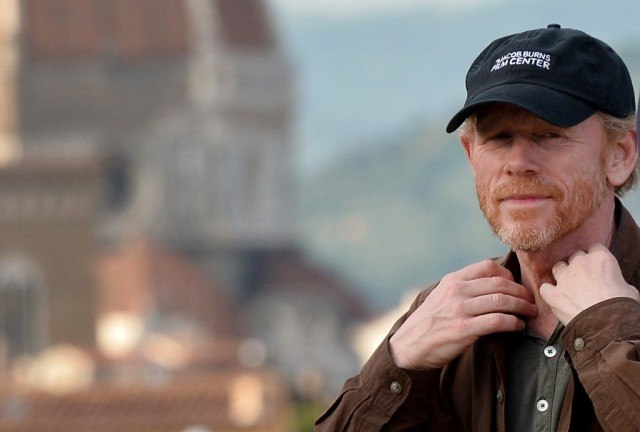 Ron Howard wearing a hat, with his hands up along his collar.