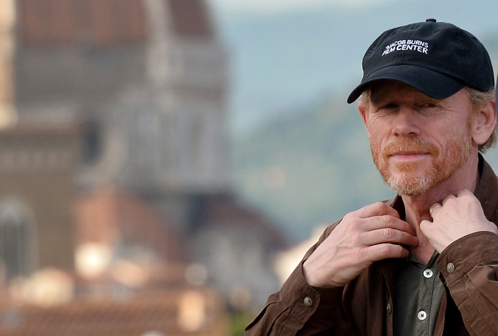 Ron Howard wearing a hat, with his hands up along his collar