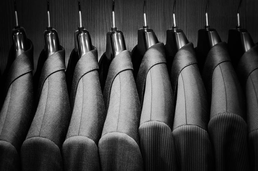 men's suit jackets hanging in a closet