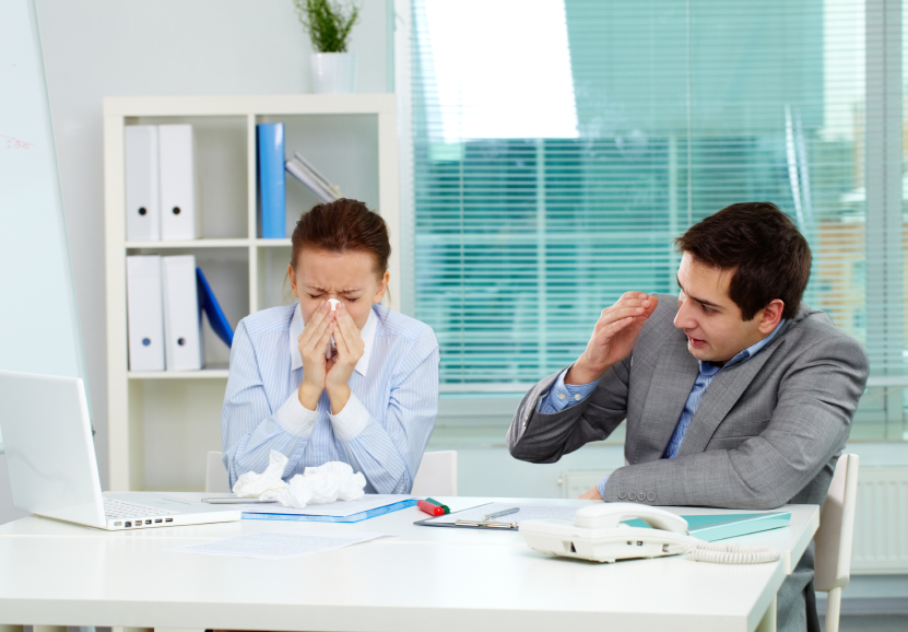 A sick woman blows her nose next to her colleague