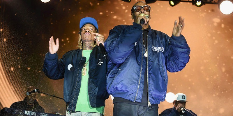 Snoop Dogg and Wiz Khalifa are rapping next to each other on stage.