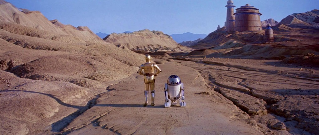 C-3PO and R2-D2 stand side by side on a deserted road