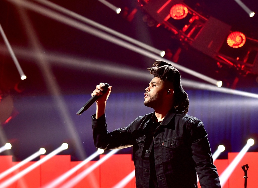 The Weeknd is on stage holding up a microphone and performing on stage.