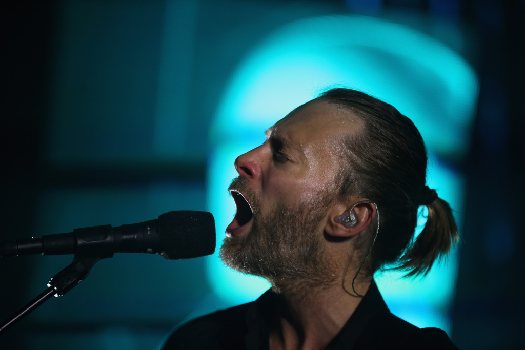Thom Yorke sings into a microphone