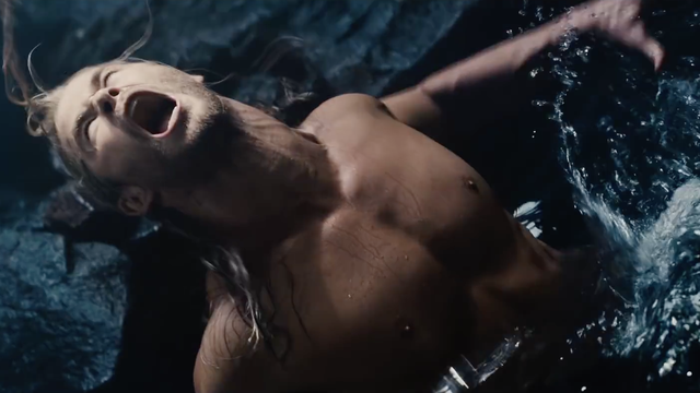 A shirtless short in a pool of water screaming, while looking upwards