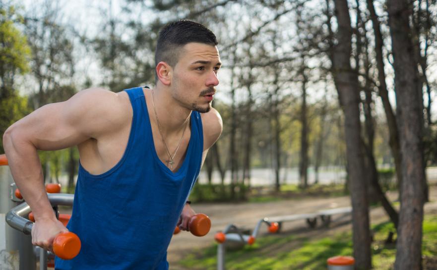 Man performing bodyweight dips at park