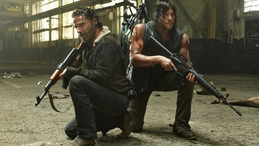 Daryl and Rick crouch down holding guns