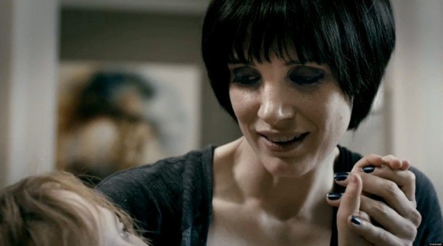 Jessica Chastain wears a black wig and holds a child's hand in Mama