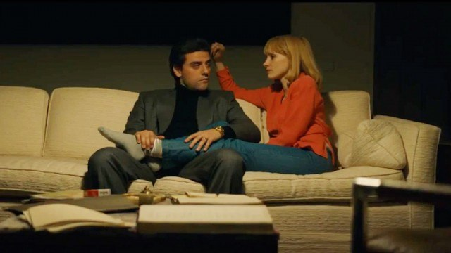 Oscar Isaac and Jessica Chastain sit together on a. couch in A Most Violent Year