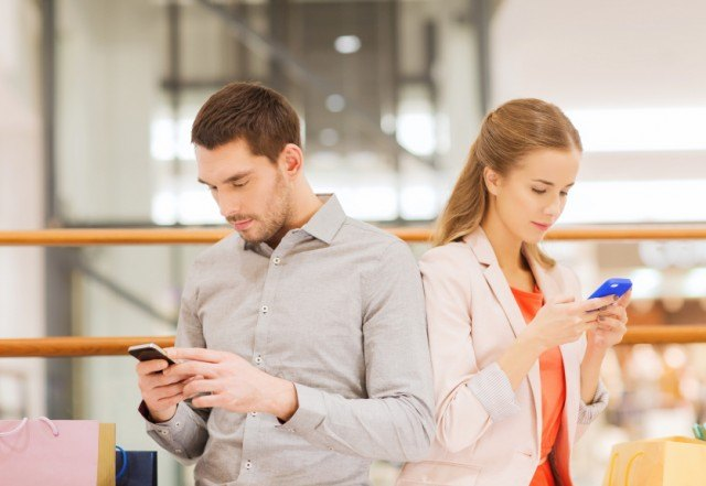 Man and woman holding mobile phones.