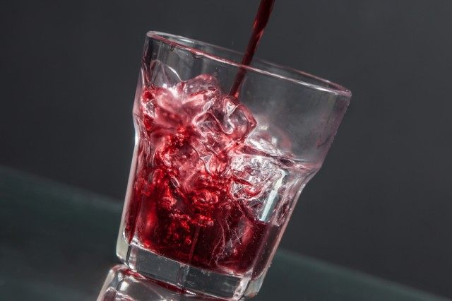 pouring cranberry juice into a glass