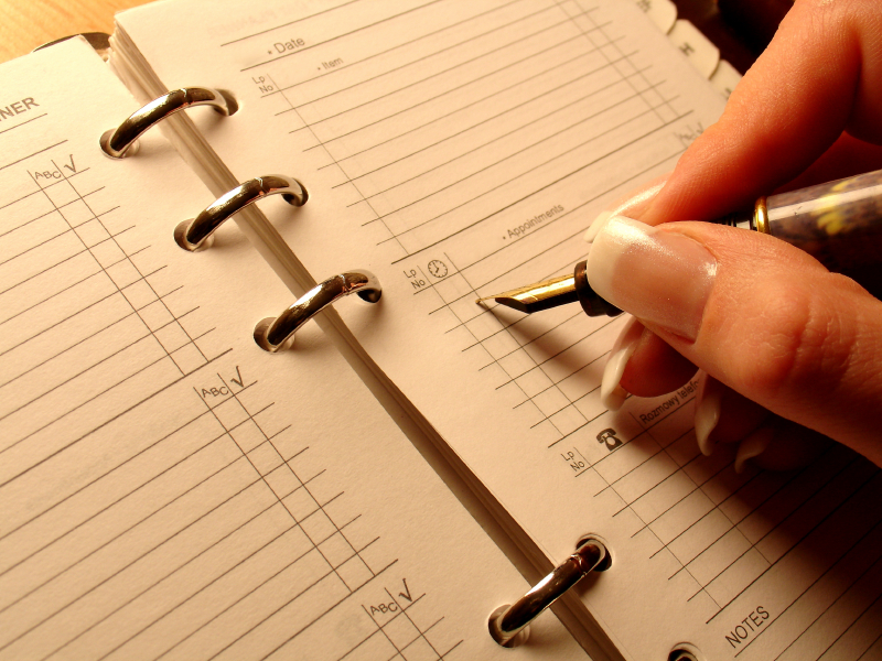 A woman writes on a schedule planner