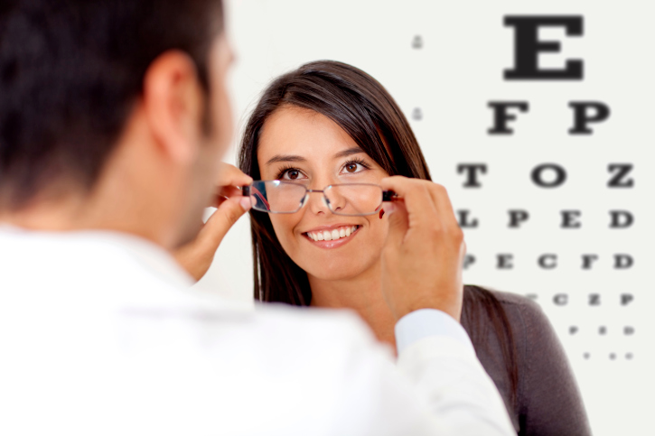 an eye doctor fitting a woman for glasses