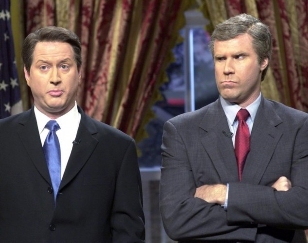 Will Ferrel in a suit and red tie looks over at his co-star while crossing his arms.