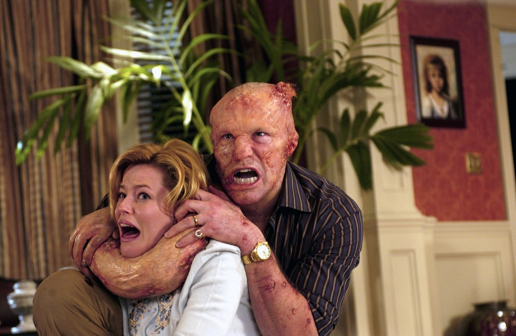 Elizabeth Banks in a living room being attacked by a grotesque transforming Michael Rooker in Slither