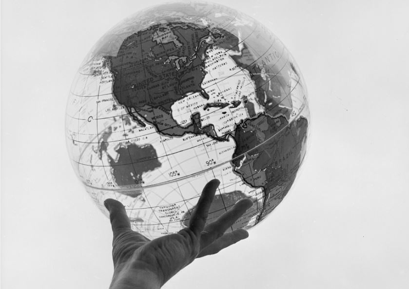 A hand holding up a globe