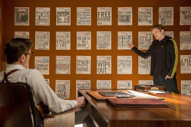 Taron Egerton in front of a wall of newspapers, pointing to one toward the middle