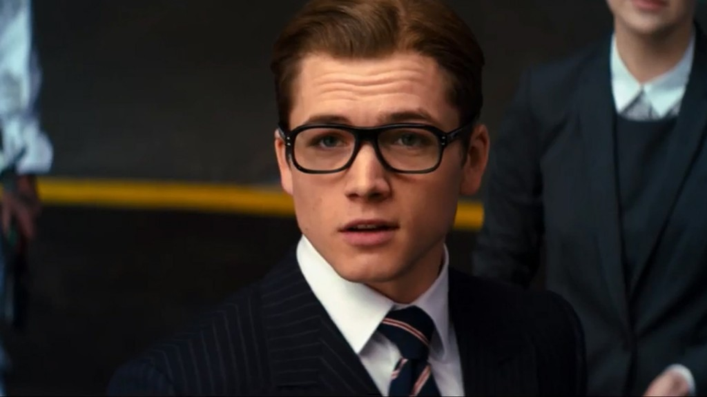 Taron Egerton wears glasses and a suit