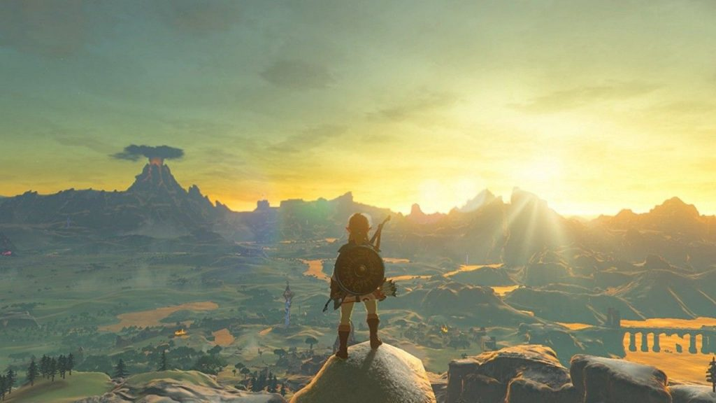 Link stands atop a mountain in Breath of the Wild