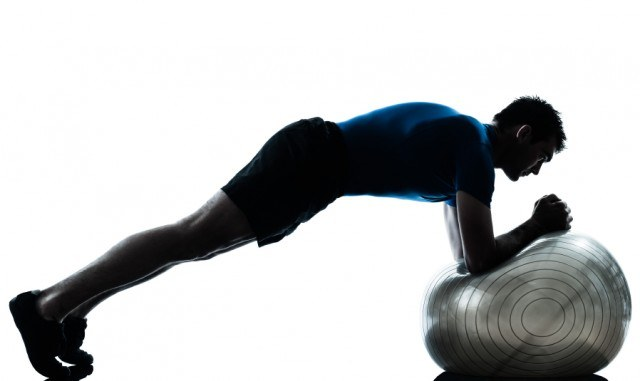 man doing planks on a stability ball