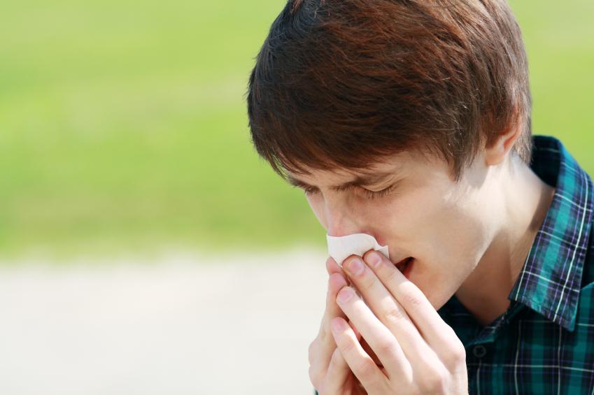 man sneezing into a tissue