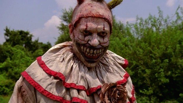 A scary, evil clown standing in front of trees in American Horror Story