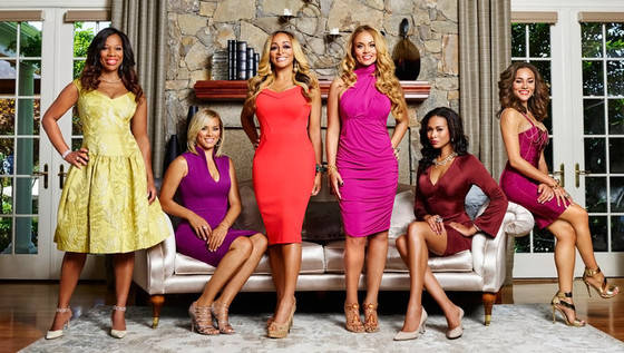 The cast of The Real Housewives of Potomac Season 1 poses in front of a fireplace
