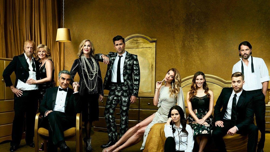 The cast of Schitt's Creek poses in a golden room