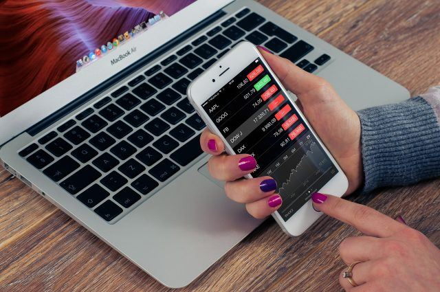 Woman checks stocks on her phone in front of a laptop