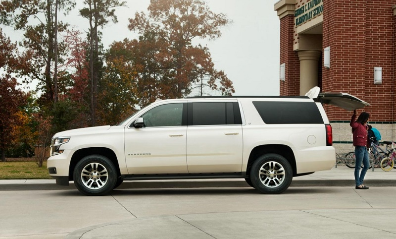 Side view of white 2016 Chevrolet Suburban from driver's side.