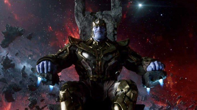Thanos sits on his throne, looking directly at the camera with a slight smile