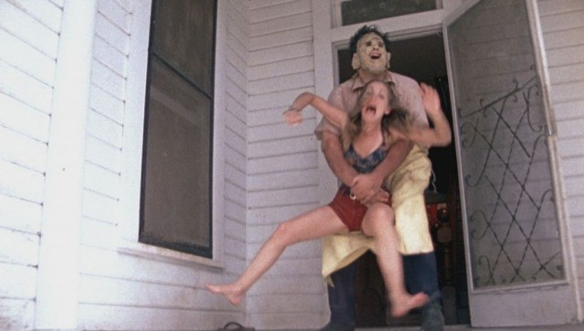 Leatherface grabs a woman from behind and drags her into a house in The Texas Chain Saw Massacre