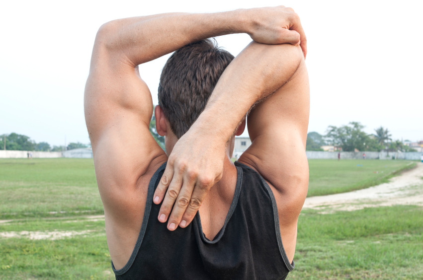 A man stretching his triceps after a workout