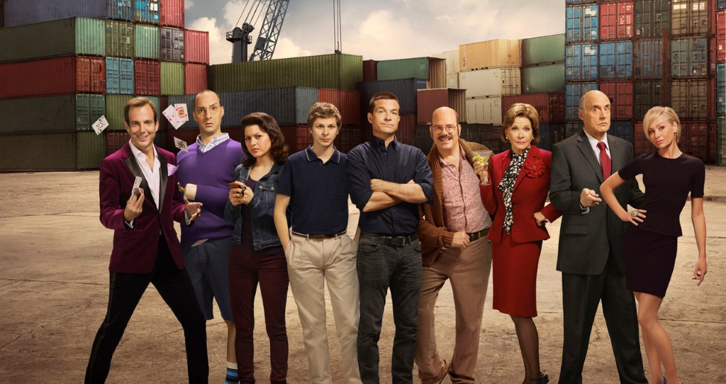 The Bluths standing together in front of shipping crates