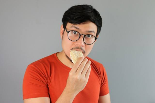 A man eating a piece of bread.